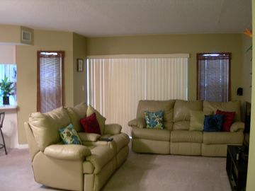 Behind vertical blinds, is screened lanai & waters edge