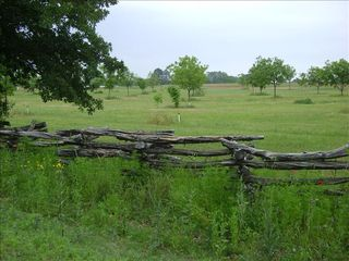 Fredericksburg farmhouse photo - a hand-built split rail fence flanks the property entrance