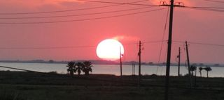 Galveston house photo - RIGHT: sunset over the bay - actual photo from our deck