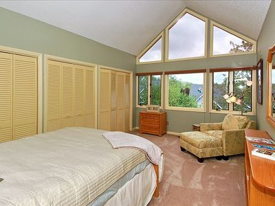 Upstairs second bedroom features queen-size bed and large picture windows.
