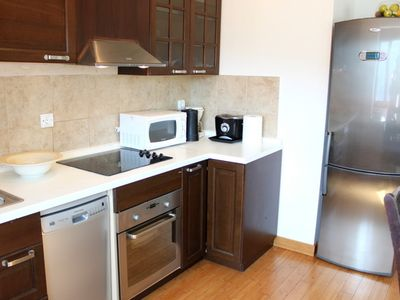 Modern kitchen with dishwasher and full-size refrigerator.