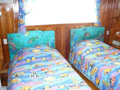 Bedroom with two twin beds, with hand painted head boards overlooking the ocean.