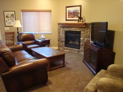 Living room with leather sofa & chairs, stone gas fireplace and HD TV.