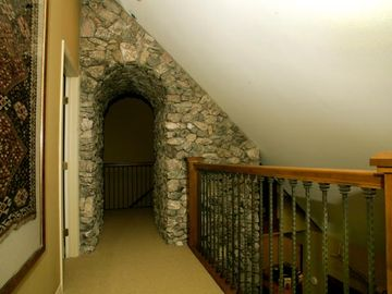 Upstairs hallway with walk thru fireplace and views down to main living room