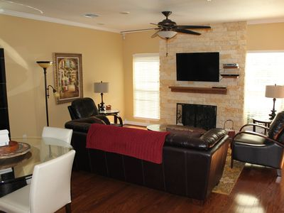 View of living room from the rear entry, showing the fireplace and television.