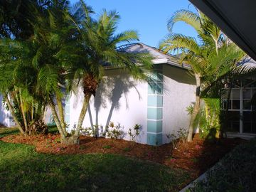 Front entrance with palms and other colorful vegetation in season.