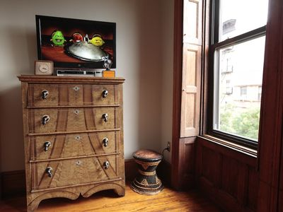 Flatscreen LED TV over the antique dresser next to the African stool.
