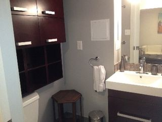 Queens studio photo - Rose wood cabinets and vanity in bathroom