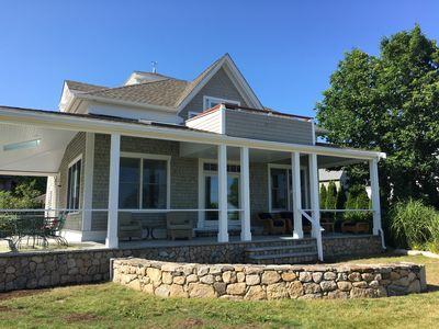 New wraparound porch & deck with water views, dining table & seating areas.