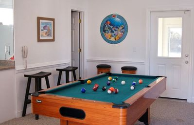 Full-size pool table in game room with wet bar, large refrigerator & microwave