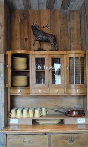 Gardiner lodge rental - stocked dish hutch with John's bronze elk sculpture