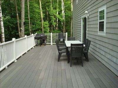 Treeline view Trex deck with grill and table.