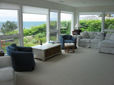 The living room with expansive views of the water and plenty of comfy seating.