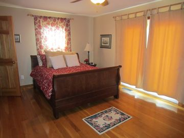 The guest room - with queen bed & doors opening to deck (& view of lake).