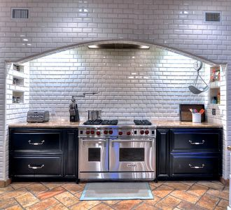 Multiple burners, water faucet and double oven in this professional kitchen.