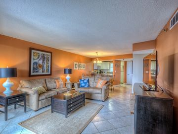 Sandestin condo rental - Living room with dining area and kitchen in background
