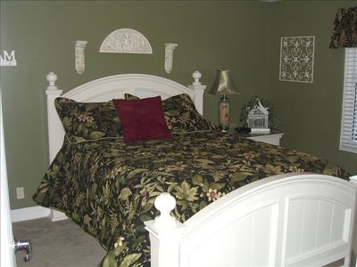 Beautiful Queen bedroom with flat screen TV mounted on wall across from bed.
