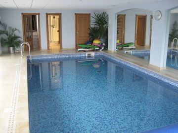 View of indoor pool with sauna & shower