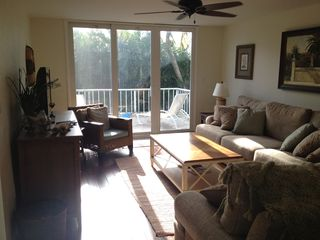 Sanibel Island condo photo - Family room and balcony with lounge chairs