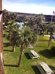 North Padre Island condo photo - View out front door of courtyard and pool with BBQ grills and picnic tables.