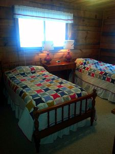 Twin beds with quilted bedding. Large TV, closet, and chest in room.