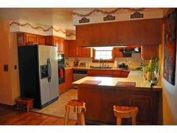 Modern kitchen with double oven and counter top stove. Dishwasher.