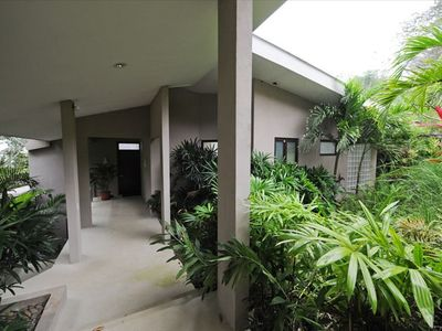 Lush Gardens around Covered Walkway to the Front Door.