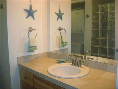 Clean updated master bath with walk-in glass brick shower.