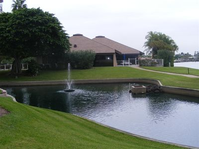 Well manicured grounds. View of fountain and clubhouse and deck entry.