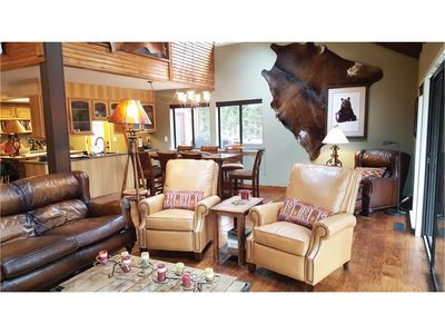 LIVING ROOM: Hickory floors, stone fireplace, leather reclining chairs