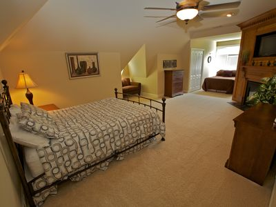 Upper level Queen bed + Full-size bed with loveseat, fireplace, and lake view.