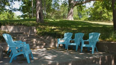 Shady riverside patio with adirondack chairs and large bench swing nearby.