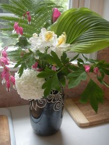 Flowers from gardens on kitchen Corian counter with marble backsplashes