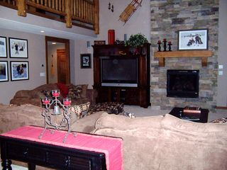 Sunriver house photo - Floor-to-ceiling stone fireplace, big-screen TV, surround sound
