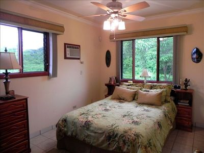 Second bedroom with queen bed, plenty of natural light and jungle/ garden view.