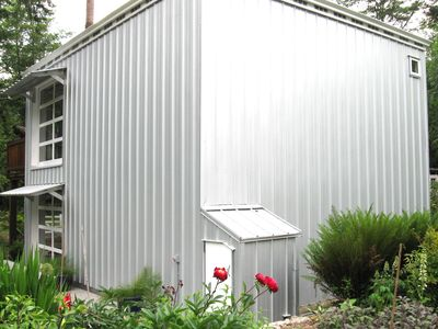 Front view of studio clad in Gavalume to create an industrial looking facade .