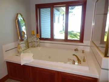 Jacuzzi tub, tiled shower with built in bench