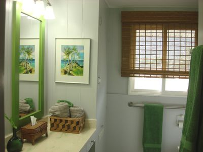 Updated bathroom features bright and cheerful colors with fresh towels.