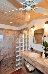 Large bathroom attached to bedroom with double vanities and walk in shower
