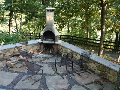 Outside fireplace with grill on lower patio.