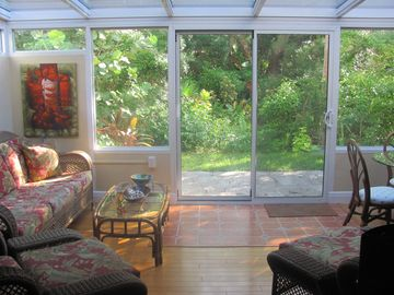 Beautiful Four Seasons Glass Sunroom with patio and garden view