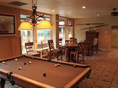 Game room has pool table and tables with chairs.