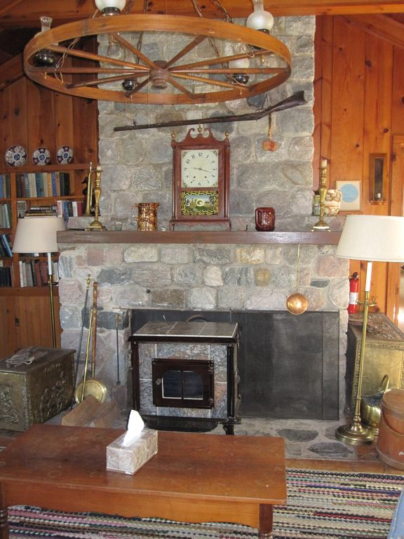 Stone fireplace with Franklin stove in living room.