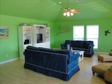 Living/den area has two sofas (one sleeper sofa) and oversized seagrass chairs