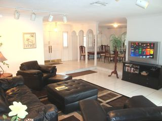 Fort Lauderdale house photo - Open living room features leather furnishings, HDTV and DVD library.