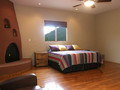 Sedona house rental - Master suite with king bed, hardwood floors, kiva gas fireplace, mountain views