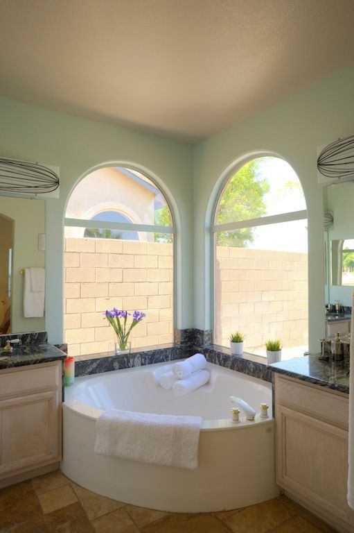 Master bath with his/her vanity on each side of the corner tub overlooking lake.