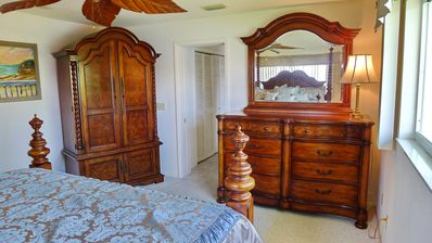 Master Bedroom w/ flat screen TV in amoire, large dresser and 2 windows to water