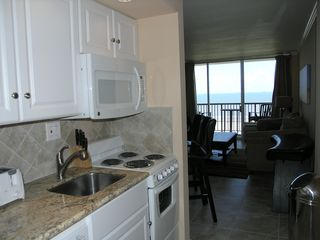 Galveston condo photo - Kitchenette has microwave, stove, oven, dishwasher, pots, pans, utensils.