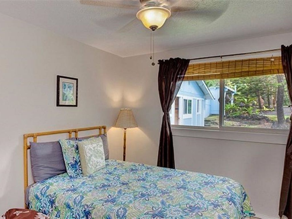 Full bed in one bedroom with overhead fan and nice window